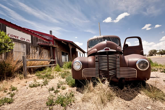 An abandoned storefront and car